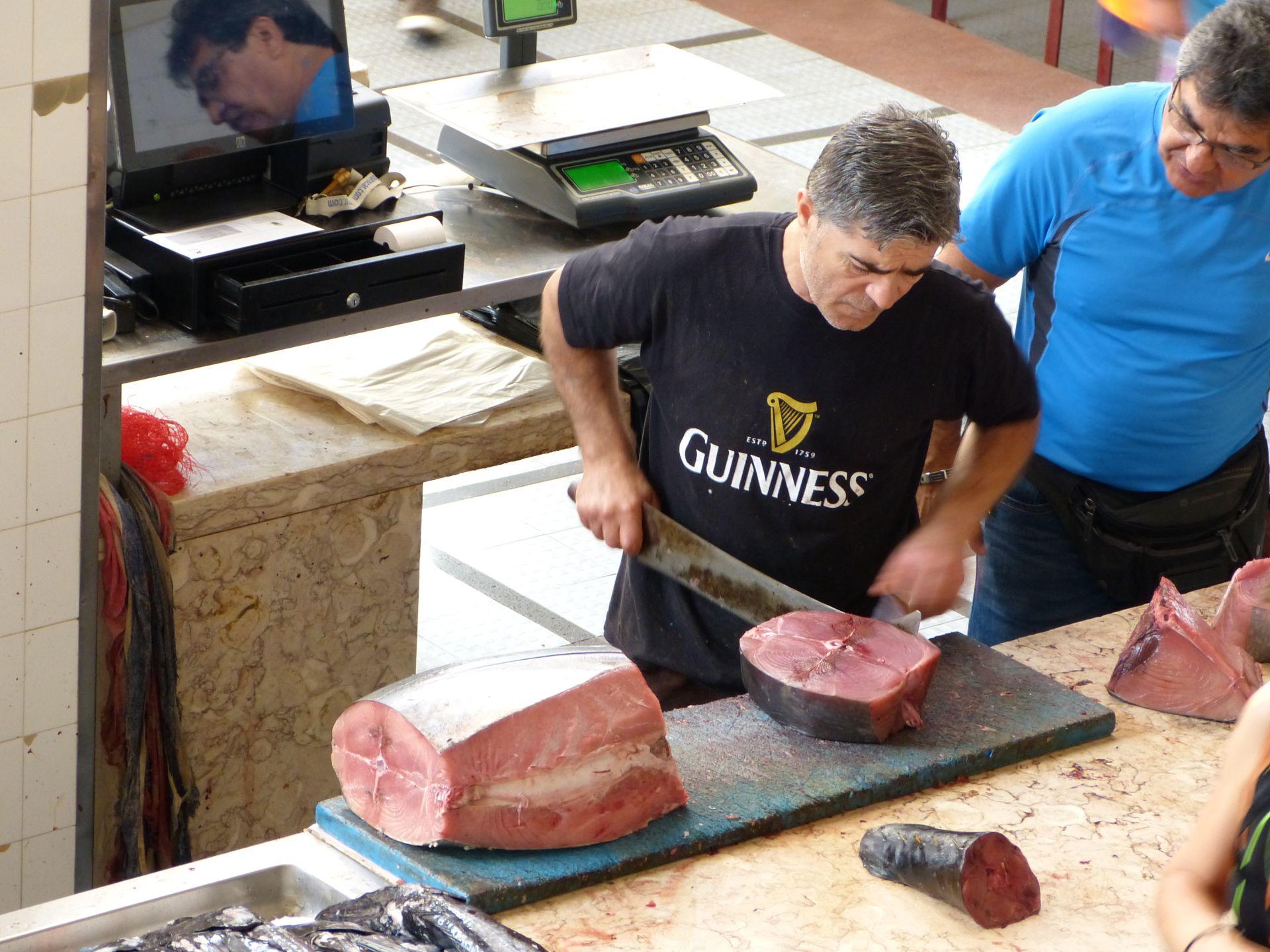 Ein Fischhändler zerkleinert Thunfisch