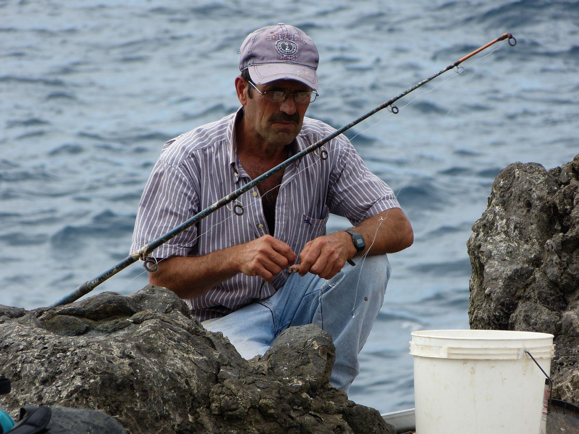 Ein Fischer auf den Vulkansteinen in Porto Moniz
